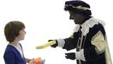 Zwarte Piet is giving presents to a child