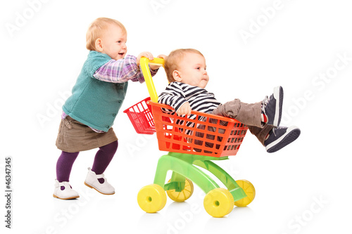 Toddler girl pushing her twin brother in a toy cart
