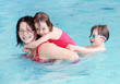 Happy family playing in a swimming pool.