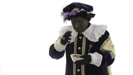 Zwarte Piet is eating and throwing gingernuts