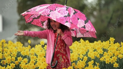Smiling young mixed race girl with umbrella extending arm in rainy daffodil field