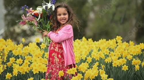 Smiling young mixed race girl holding bouquet of flowers and looking at camera in daffodil field