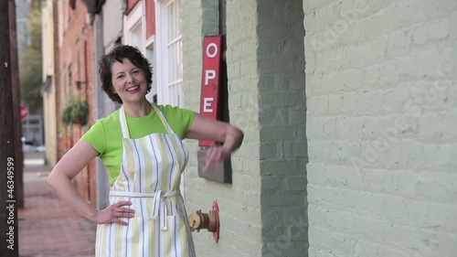 Proud Caucasian small business owner in apron emerging from shop and looking up and pointing