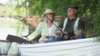 Smiling Caucasian couple fishing in rowboat on river
