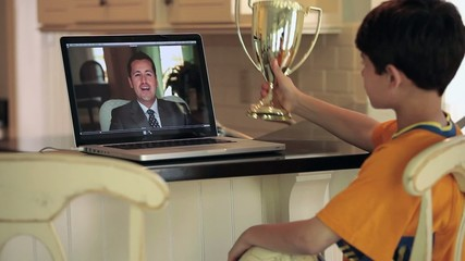 Young boy in soccer uniform video chatting with father on laptop and showing father trophy
