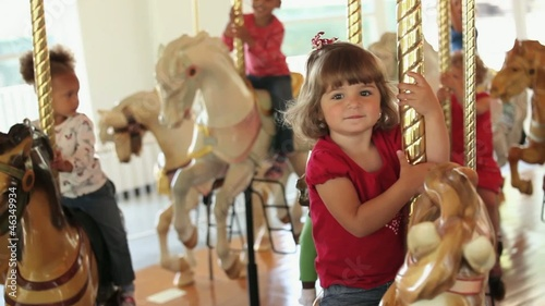 Group of smiling young girls riding carousel horses