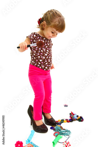 Little girl and big shoes isolated on white background
