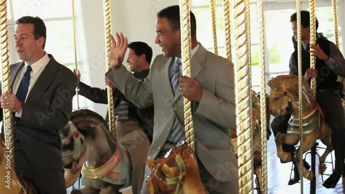Group of smiling businessmen in suits riding carousel horses