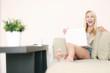 Frau auf der Couch mit Laptop freut sich