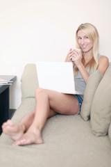 Frau auf der Couch mit Laptop und Tasse
