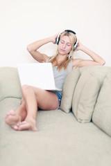 Frau auf der Couch mit Laptop und Kopfhörern