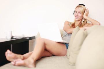 Frau liegt mit Laptop und Kopfhörer auf der Couch