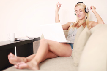 Frau auf der Couch mit Laptop hört Musik