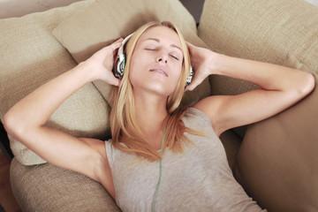 Frau liegt auf der Couch und hört Musik