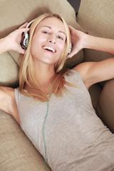 Frau liegt auf der Couch mit Kopfhörern