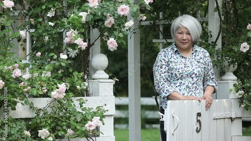 Smiling Japanese woman standing at garden gate and looking at camera