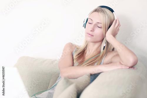 Frau auf der Couch hört Musik