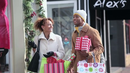 Couple in warm clothing Christmas shopping on urban street