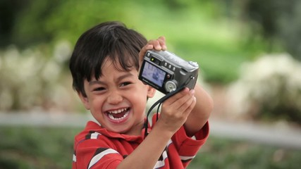Young Asian boy playing with digital camera