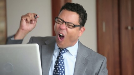 Excited Hispanic businessman celebrating at laptop in office