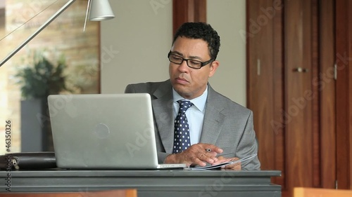 Hispanic businessman using laptop and writing on pamphlet at desk in office