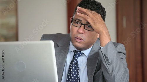 Disappointed Hispanic businessman using laptop in office