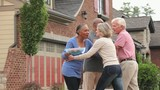 Senior couple greeting friends outside new house