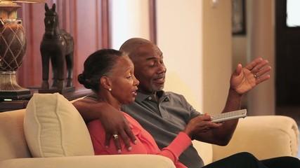 Senior Black couple watching TV on sofa in living room