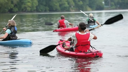 Mature couples kayaking on river