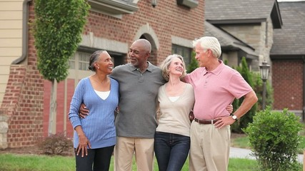 Smiling senior couples standing in front of new house