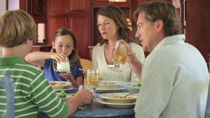 Caucasian family eating dinner at kitchen table