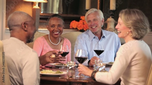 Mature couples eating dinner and drinking wine in dining room