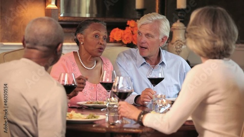 Mature couple talking while eating dinner and drinking wine in dining room