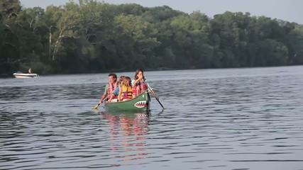 Caucasian family rowing canoe in river