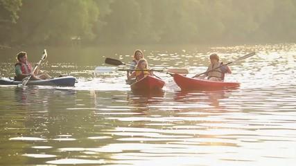 Caucasian family in kayaks on river
