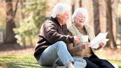 Senior Caucasian couple drinking coffee and discussing paperwork on lawn