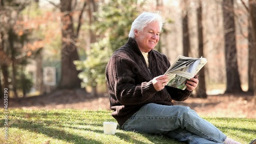 Smiling senior Caucasian man drinking coffee and reading newspaper on lawn