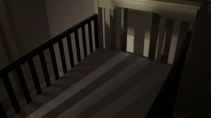 Empty crib in dim nursery