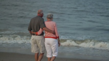 Senior Caucasian couple hugging on beach and looking at ocean