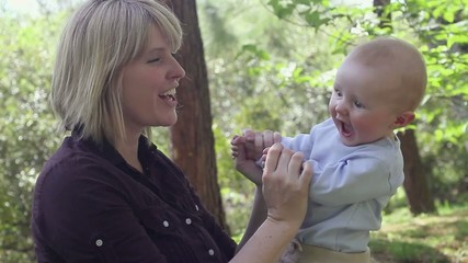 Caucasian mother kissing baby in park