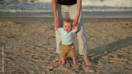 Caucasian mother and baby holding hands on beach