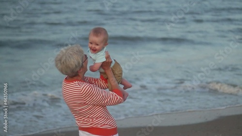 Caucasian grandmother holding baby on beach