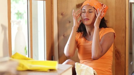 Hispanic woman rubbing her head