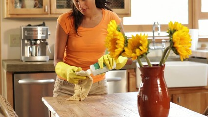 Hispanic woman cleaning the counters in her kitchen