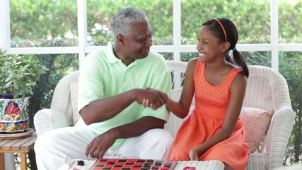 Black grandfather and granddaughter playing checkers