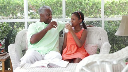 Black grandfather and granddaughter having lemonade on the porch