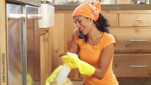 woman talking on the phone while cleaning her kitchen
