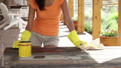 Hispanic woman staining a wood table