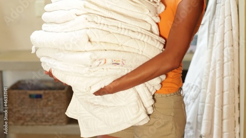 Hispanic woman holding a stack of towels in her home