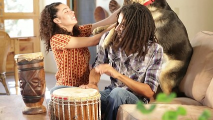 Young mixed race couple playing drums with their dog